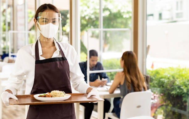 Asian waitress serving food new normal. stock photo