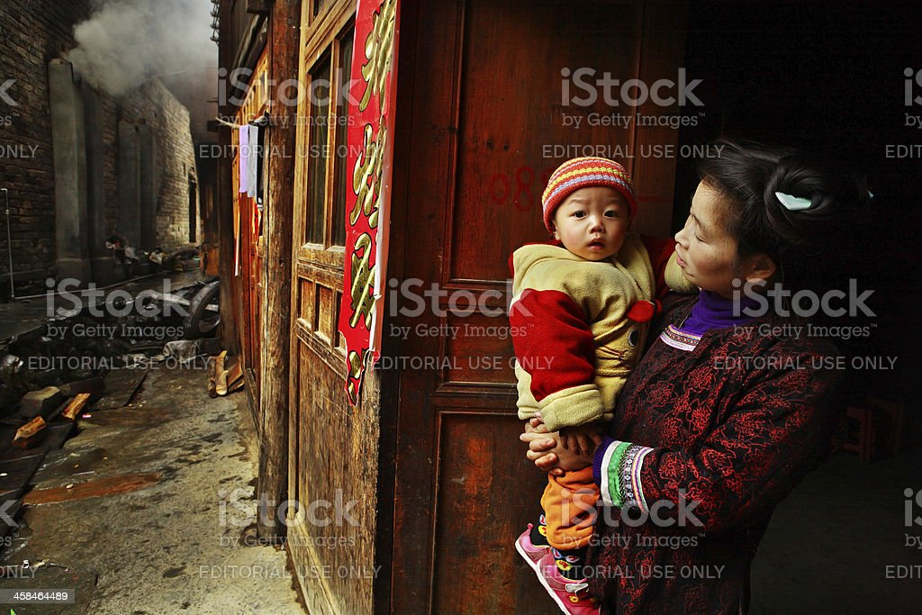 Asian with baby in her arms, stands on rural street. stock photo