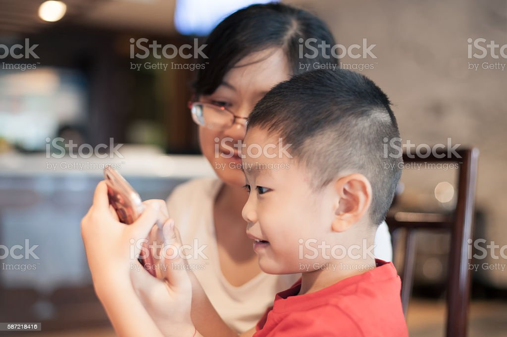 Asian woman and child look at smart phone stock photo