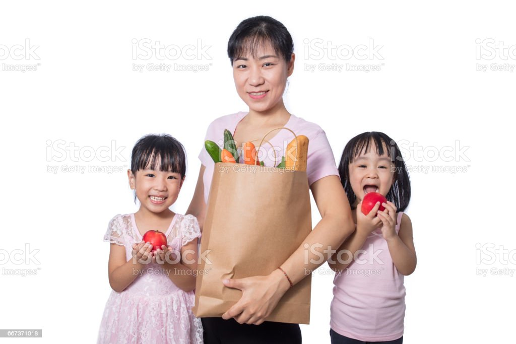 Asian Woman and daughters carrying groceries stock photo
