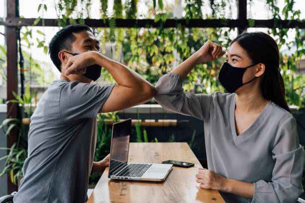Asian woman and man friends wearing face mask outdoors. Friends greeting and shaking with elbows as new normal.  Corona Virus - Covid 19 elbow bumps greeting style to prevent contact and virus spread stock photo