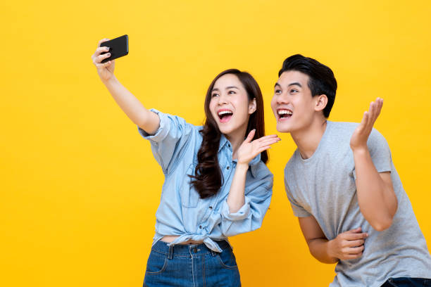 Asian woman and man taking selfie on yellow background. stock photo