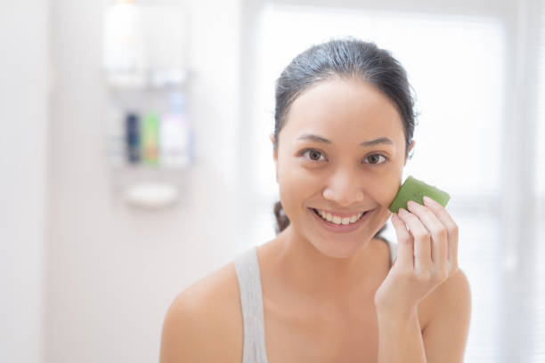 Asian woman Apply aloe vera to her face in the bathroom. stock photo