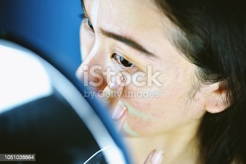 istock Asian woman applying cosmetics makeup and using color correction concealer, Learning doing self makeup. 1051038864