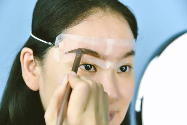 Asian woman applying cosmetics makeup, Eyebrows template head strap use for shaping and thickening perfect brows, Learning doing self makeup. stock photo