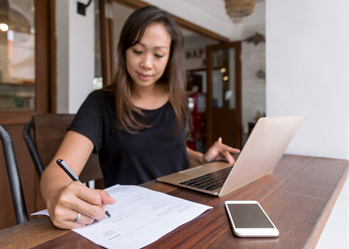Portrait shot of Asian woman applying for a new job, filling print out application form during home quarantine Covid 19