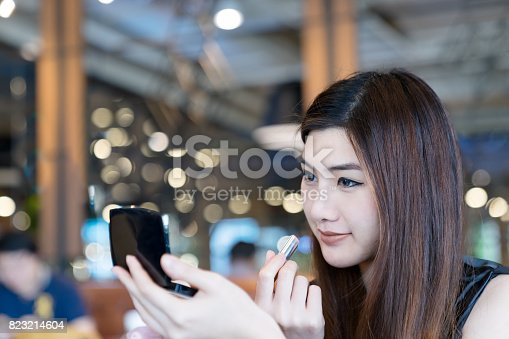 istock Asian woman applying lipstick and looking pocket mirror at coffee shop. Cute girl makes makeup. 823214604