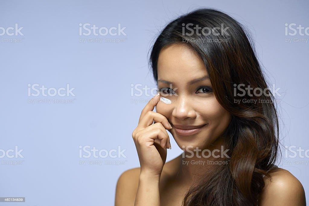 Asian Woman Applying Moisturizer stock photo