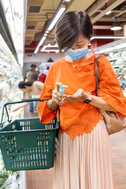 Asiatische Frau, die Desinfektionsmittel zur Hand zum Schutz vor Viruskeimen aufwendet – Foto