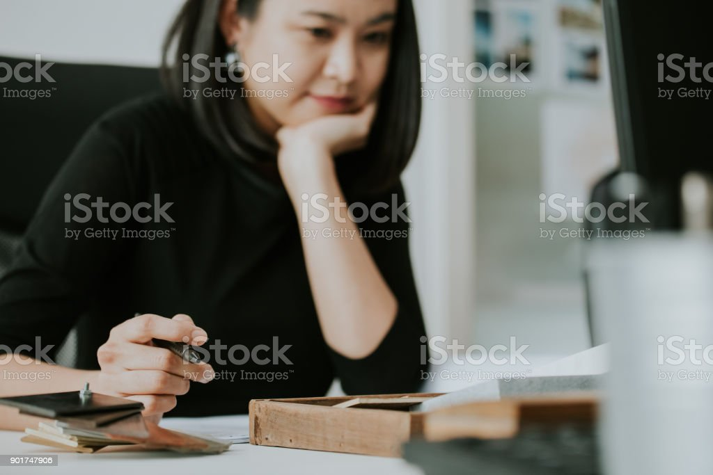 Asian woman architect is enjoy her work with material board stock photo