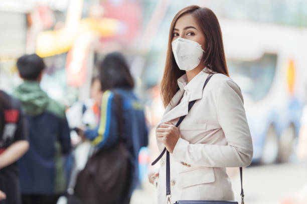 Asian woman are going to work.she wears N95 mask.prevent PM2.5 dust and smog stock photo