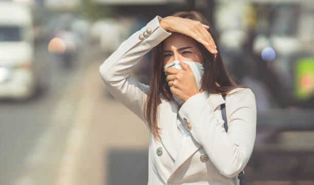 Asian woman are going to work.she wears N95 mask.prevent PM2.5 dust and smog.she is coughing stock photo