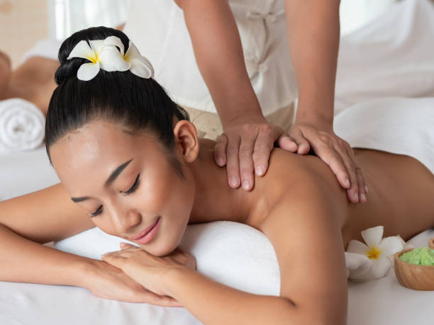 Asian woman are relaxing shoulder massage in the Spa Salon. Thai massage for health. Select focus hand of masseuse stock photo