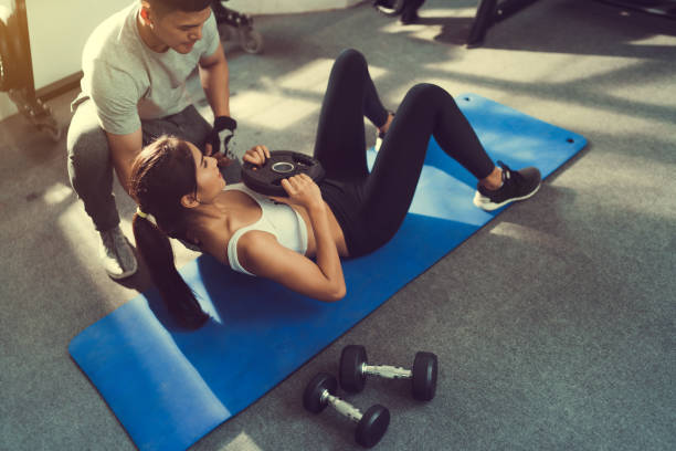 Asian woman are sit-up with added weight on her more and more trainer are there to help. stock photo
