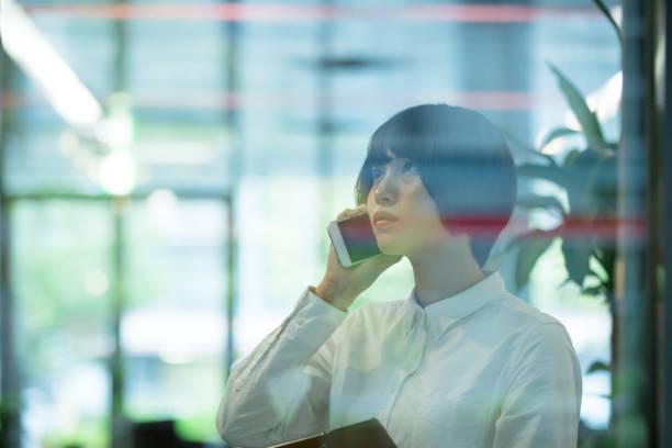 アジアの女性は、事務所の窓からビルでスマート フォンを使用しています。 ストックフォト