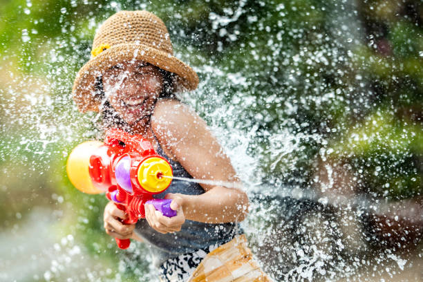 Asian woman are using water guns play in the Songkran festival stock photo