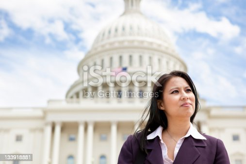 A Vietnamese businesswoman in her 30s looking away in front of the US Capitol building in Washington, DC.