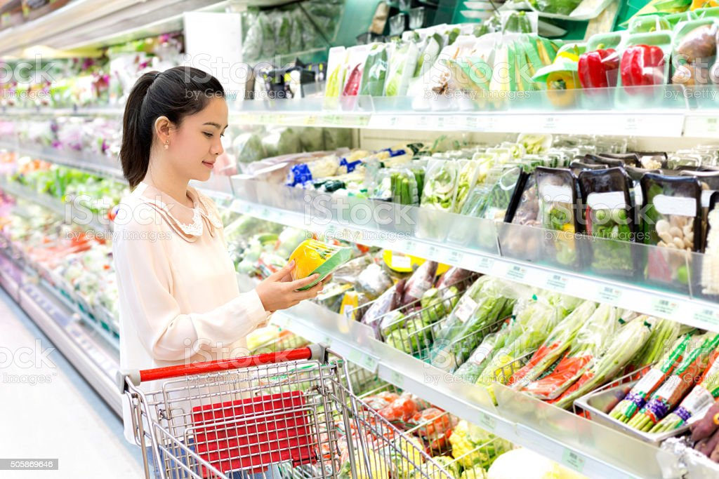 asian woman attentively considers vegetables in shop stock photo