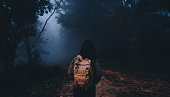 Asian woman backpacker at foerest on natural trails in morning,Vacation holiday at rain forest.