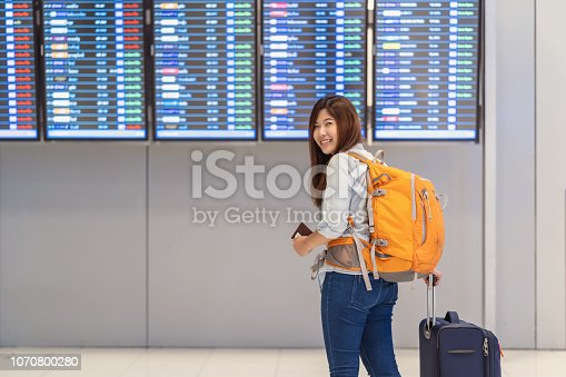 842907838 istock photo Asian woman backpacker or traveler with luggage with passport walking over the flight board for check-in at the flight information screen in modern an airport, travel and transportation concept 1070800280