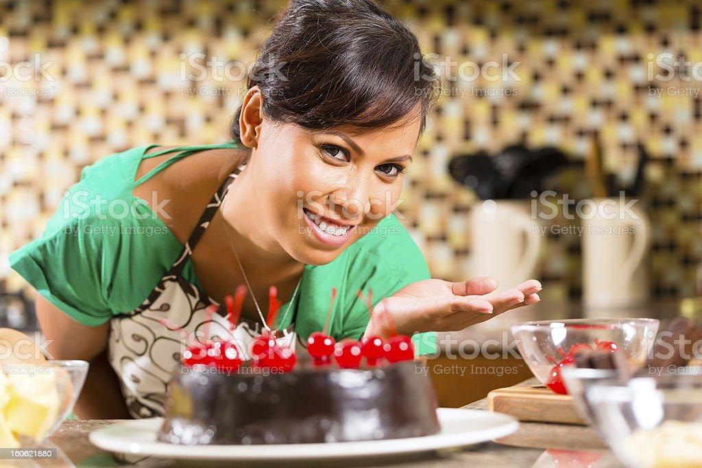 Asian woman baking chocolate cake in kitchen royalty-free stock photo