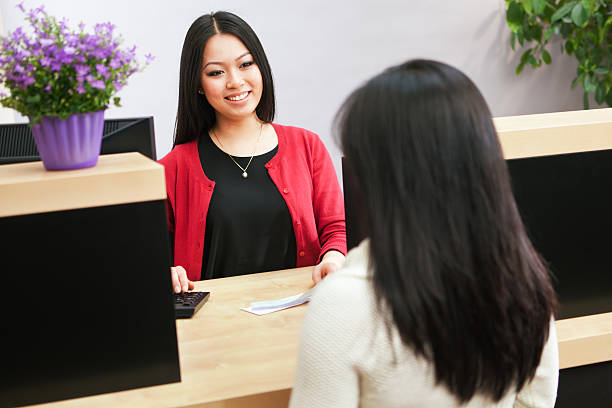 Asian Woman Bank Teller Serving Customer Approaching Retail Banking Counter stock photo