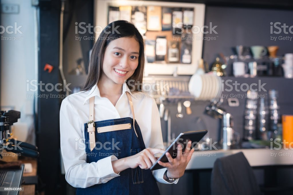 Asian woman barista smiling with tablet in her hand,Female employees are taking orders from online customers stock photo