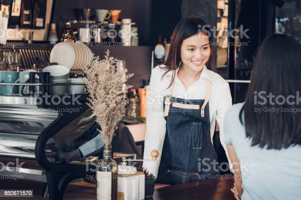 Asian woman barista wear jean apron holding coffee cup served to at picture id832671570?b=1&k=6&m=832671570&s=612x612&h=myqrloymfau4xst8h64hsokiq3fh412qjwiidxvuhgy=