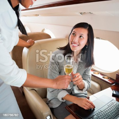 istock Asian woman being offered a glass of wine on a plane 180756762