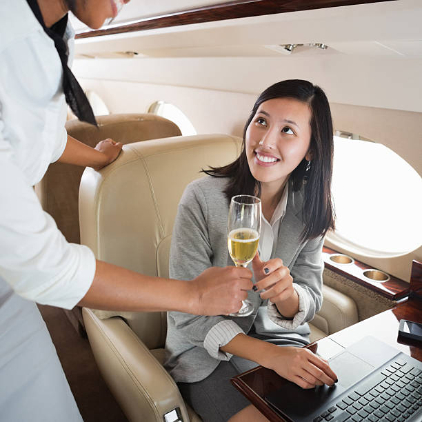 Asian woman being offered a glass of wine on a plane stock photo