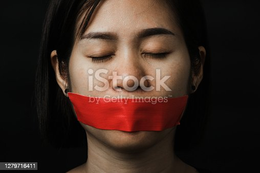 Asian woman blindfold wrapping mouth with red adhesive tape on black background. Freedom speech censorship and stop talk, International Human Right day