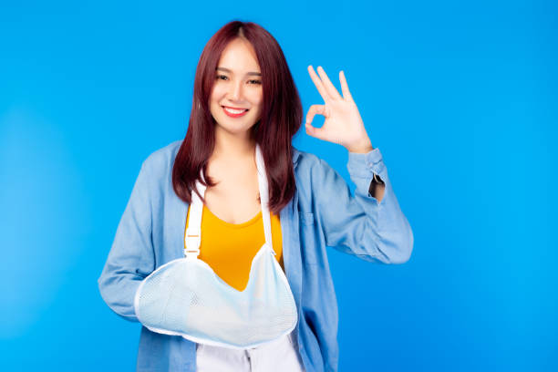 Asian woman broken arm or get dislocated at arm but pretty girl still okay because she get good insurance for take care very well. Attractive beautiful young lady get happiness. health care, insurance stock photo