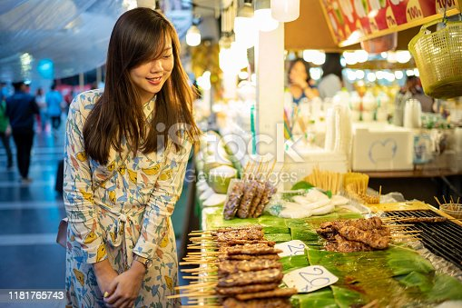 Asian woman buy Thai style pork barbecue stick from street vendor