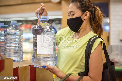 Portrait shot of Asian woman with face mask picking up purified water gallon from retail display in the supermarket amidst post pandemic Covid 19