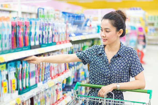 Asian woman buys a toothbrush stock photo