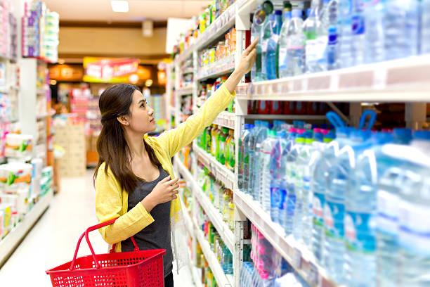 Asiatische Frau kauft im Supermarkt Flasche Wasser – Foto