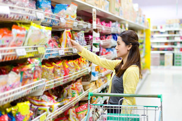 Asian woman buys in the supermarket candy stock photo