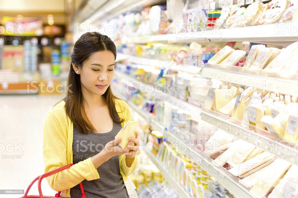 Asian woman buys in the supermarket cheese. stock photo