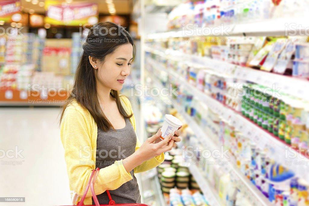 Asiatische Frau kauft im Supermarkt Joghurt. – Foto