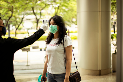 security guard measuring temperature of young woman  with infrared thermometer before entering a office, in Jakarta.