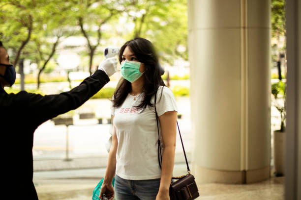 Asian woman checked with thermometer to control the temperature required to be checked in quarantine security guard measuring temperature of young woman  with infrared thermometer before entering a office, in Jakarta. thailand mall stock pictures, royalty-free photos & images