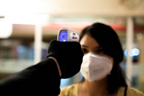 asian woman checked with thermometer to control the temperature required to be checked in quarantine stock photo