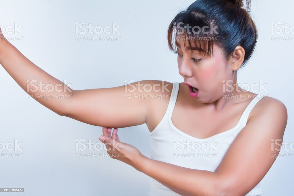 asian woman checking her fat upper arm and she agape stock photo