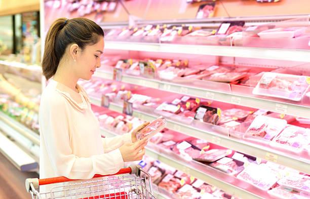 Asiatische Frau wählt Fleisch im Laden. – Foto