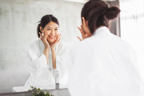 亞洲婦女清潔面前的鏡子, 皮膚護理和化妝品去除的概念 - 亞洲 個照片及圖片檔