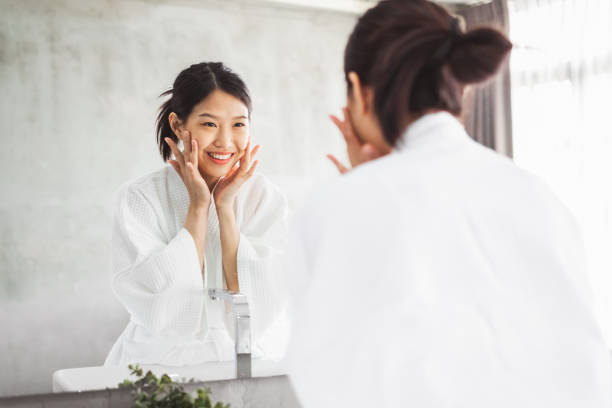 Asian woman cleaning face front of mirror, skin care and cosmetic removal concept Asian woman cleaning face front of mirror, skin care and cosmetic removal concept routine stock pictures, royalty-free photos & images
