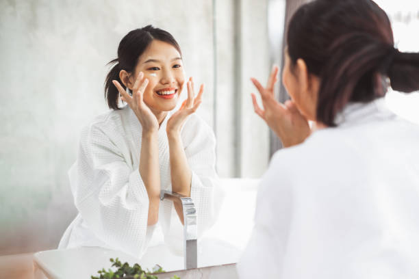 Asian woman cleaning face front of mirror, skin care and cosmetic removal concept stock photo