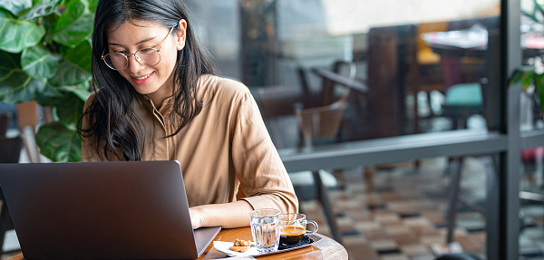 Beautiful young Asian woman wearing glasses using a laptop pc at a coffee shop.