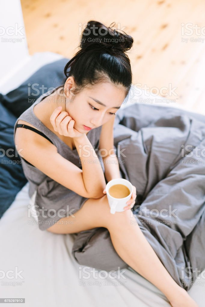 Asian Woman Contemplating in Bed stock photo