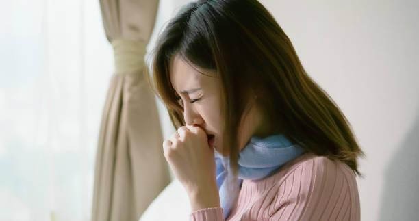 寝室でアジアの女性咳 - くしゃみ 日本人 ストックフォトと画像